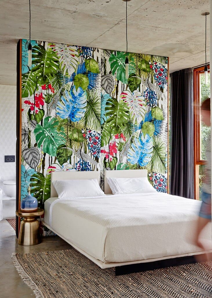 This primary bedroom boasts an accent wall with foliage wall art that's bursting with colors. It has concrete flooring and white distressed ceiling.