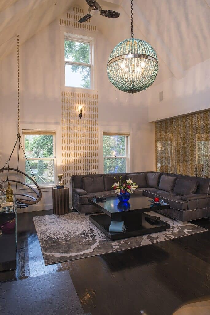 A living room under the home's tall ceiling. It offers a stylish L-shape sofa situated on top of an area rug with a center table, set on the hardwood flooring.