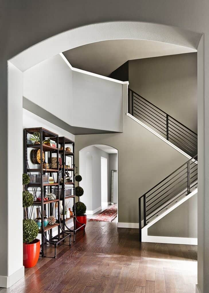 Gray foyer with hardwood flooring and an open archway beside the staircase. It includes a pair of tall shelving with decors and potted plants.