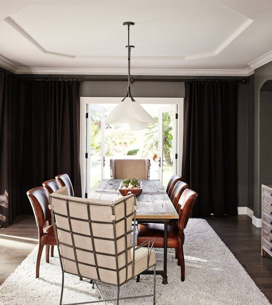 This dining room showcases a tray ceiling and glazed windows covered with black draperies. It includes a wood plank dining table paired with brown leather and metal framed chairs.