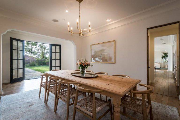 Dining space designed with a brass chandelier that hung over a wooden dining table paired with rattan chairs.