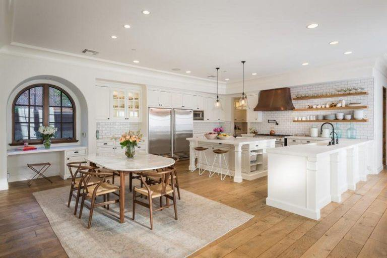 Gorgeous white kitchen with wide-plank wood floor, arched glass windows, beveled white subway tiles, wood range hood, floating shelves and a breakfast island paralleled to the dining table.