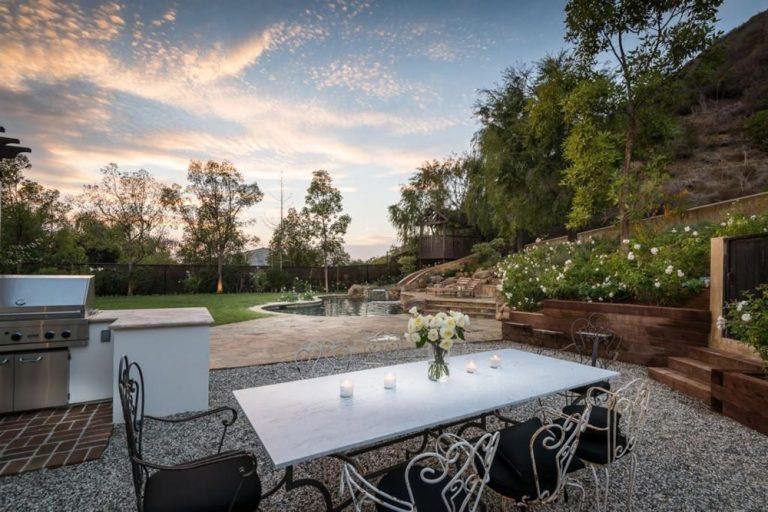 This home has a glamorous backyard with its outdoor kitchen and dining along with the pool and patio area.