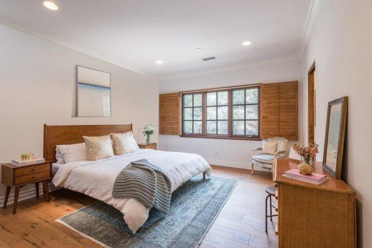 This guest bedroom is a relaxing retreat in white with traditional furniture and transitional light wood floor.