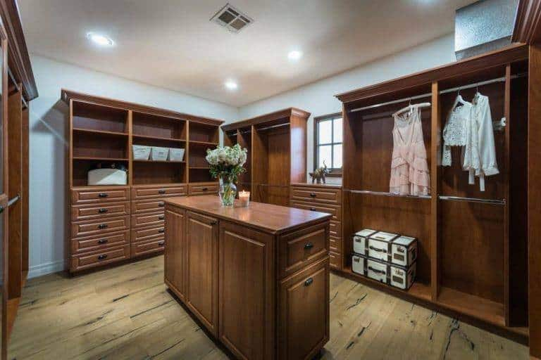 Bedroom closet with brown cabinetry and hardwood flooring. White walls and ceiling looks perfect together with the recessed lights.