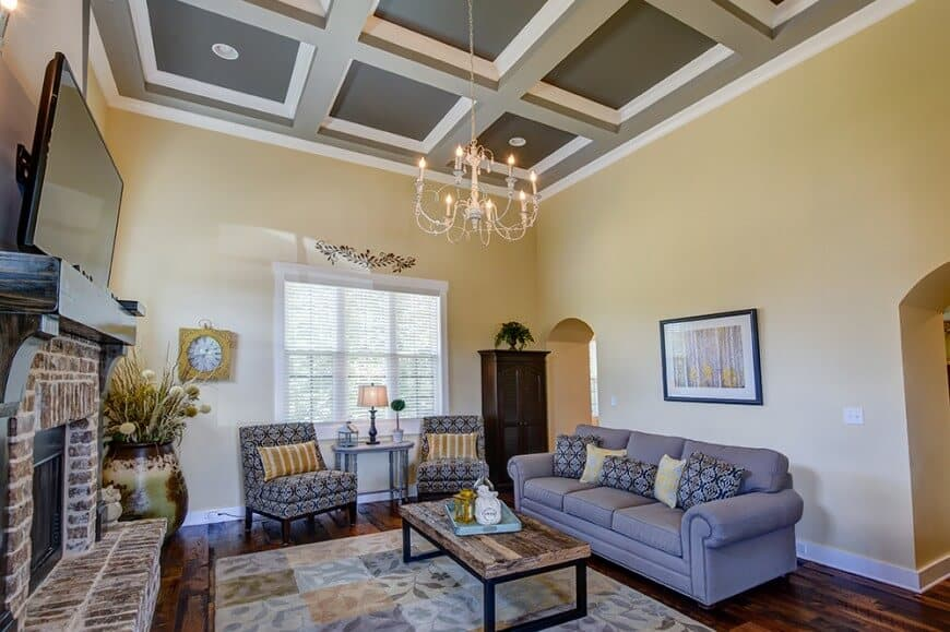 Yellow living room highlighted by a gorgeous wooden coffered ceiling with a hanging candle chandelier. It has a rustic coffee table and a bluish gray sofa with patterned pillows that match with the chairs.
