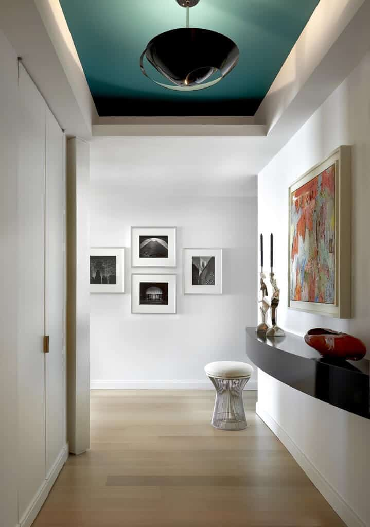 Small foyer with White walls and green ceiling offering a very elegant lighting and wall decors.