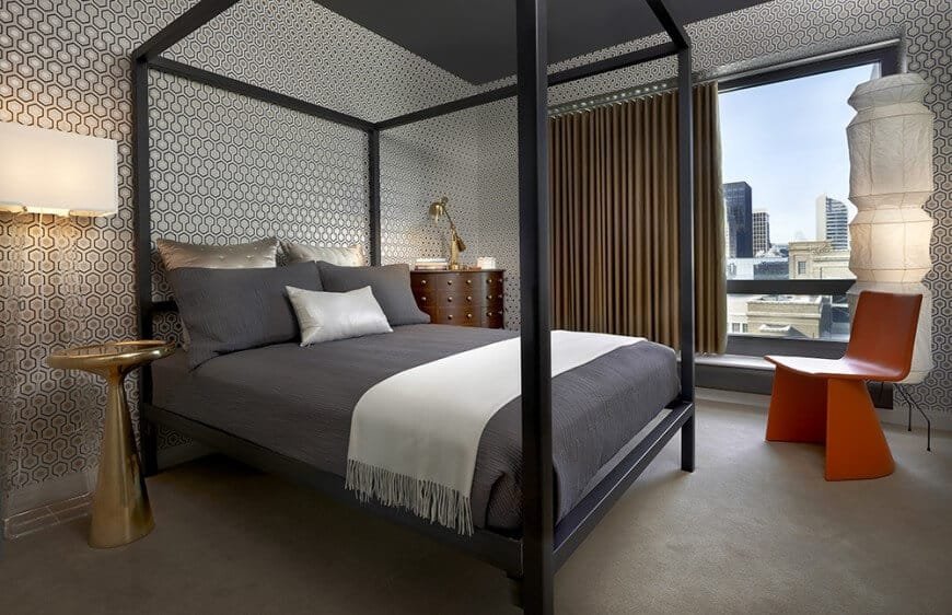 Contemporary guest bedroom offers a metal canopy bed accompanied by a modern red chair, wooden nightstand and a gold side table that adds a hint of class in the room.