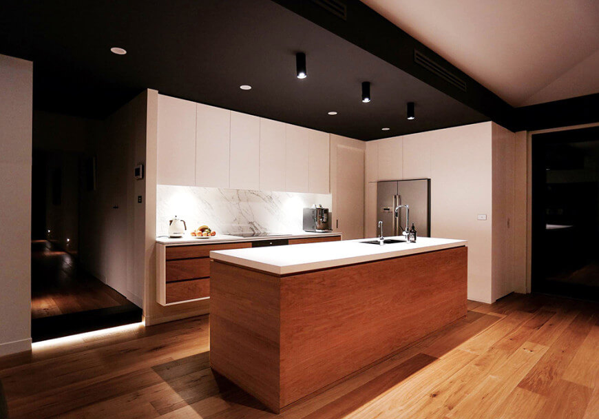 Contemporary kitchen setup featuring a hardwood flooring and black ceiling combined with the white walls. The counters are made of smooth white marble. The narrow center island is lighted by recessed ceiling lights.