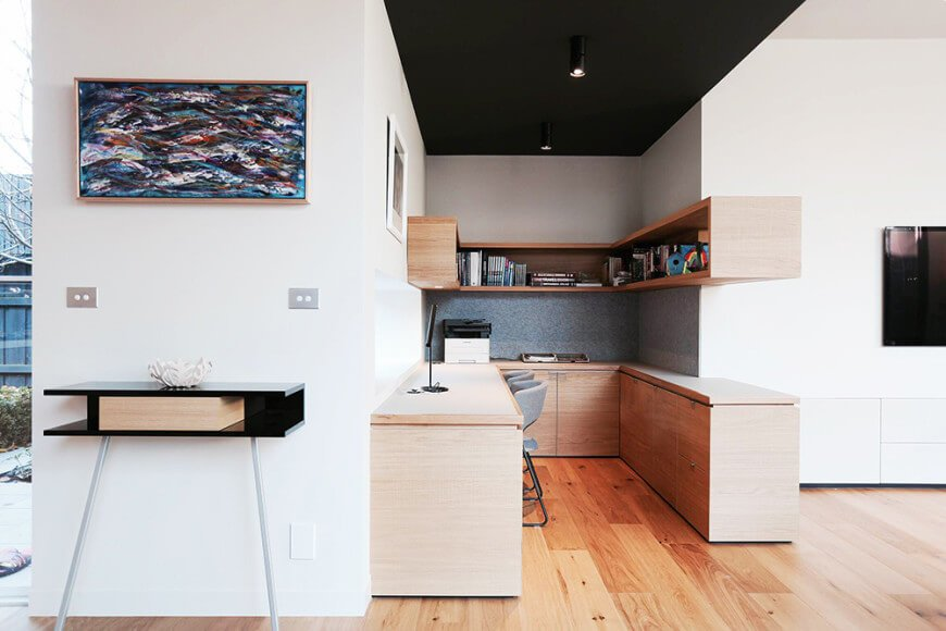 Small home office situated in between white walls offering built-in wooden floating shelf and U-shaped desk with gray chairs.