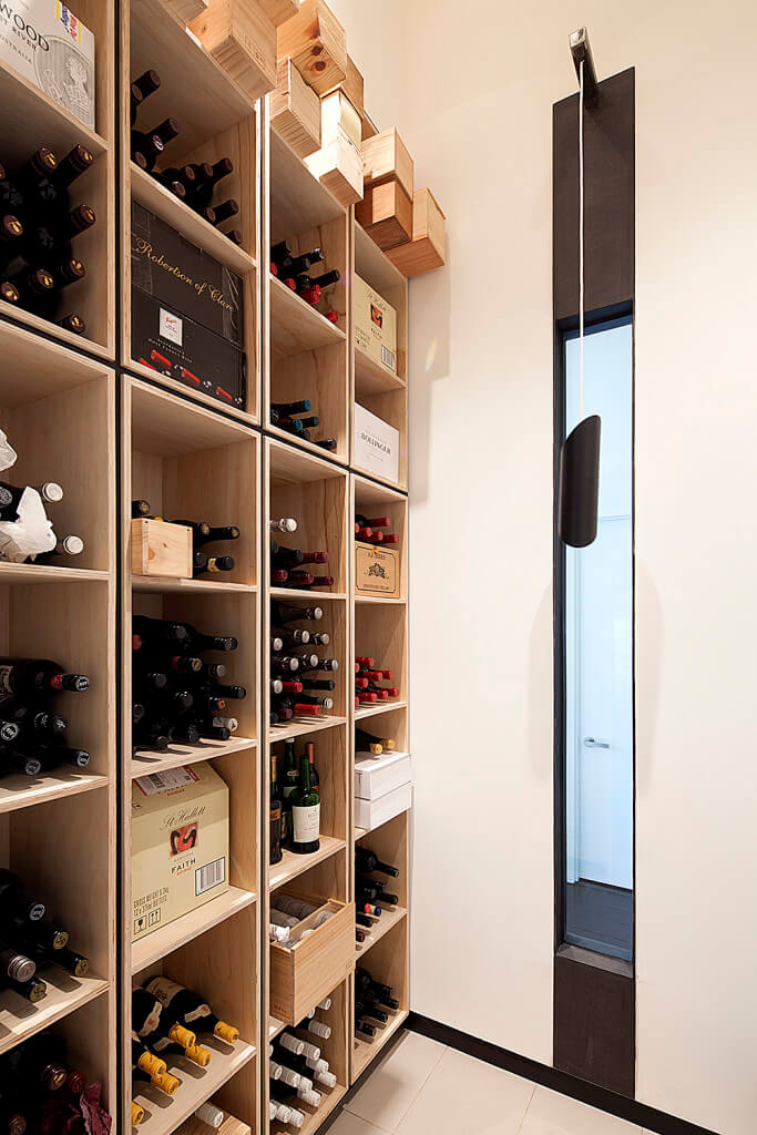 A tall light wood wine shelves with storage boxes at the top. It is placed in the corner of white walls lined with a vertical glass that lets you peek on the outside.