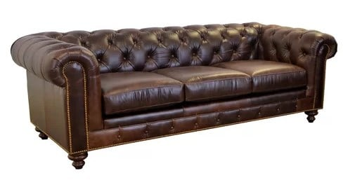 Tufted chesterfield sofa with rounded arms and loose cushions.