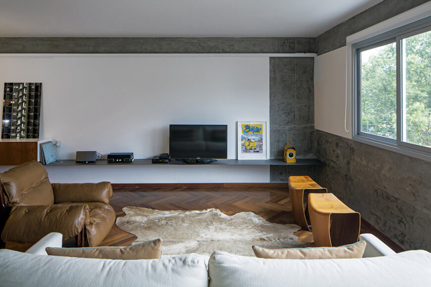 This living room features concrete walls framed with white panels and a herringbone wood flooring topped with a cowhide rug.