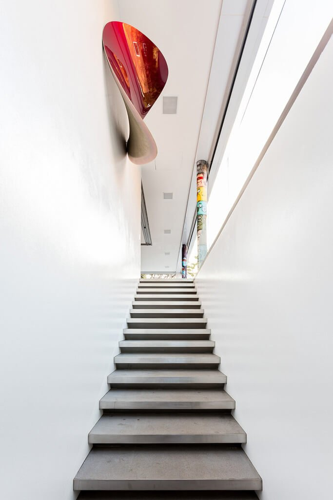 Concrete straight staircase fixed to the white walls and accented by colorful concave artwork.