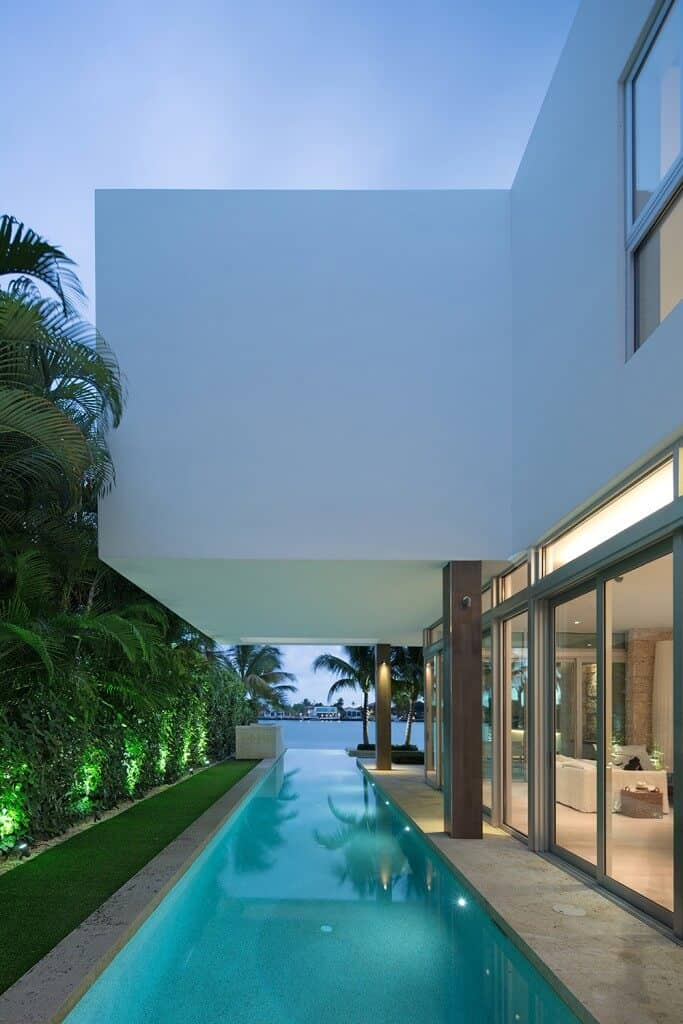 This modern house with full height glazing that's framed with wooden columns offers a lap pool lined with a vertical lawn and hedge plants for optimum privacy.