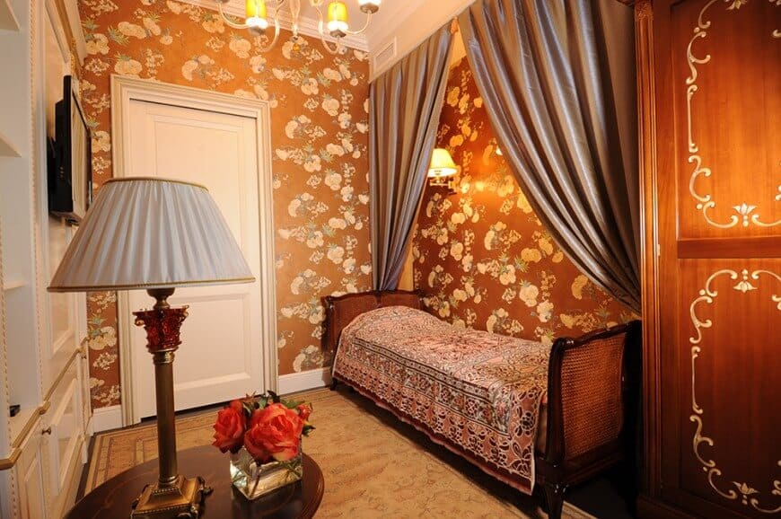 Warm guest bedroom clad in brown floral wallpaper offers a Cleopatra daybed and round end table topped with a table lamp.