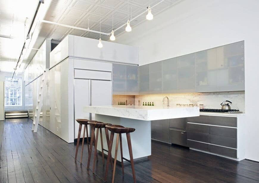 Industrial kitchen lighted by bulb pendants that hung from the ornate white ceiling with exposed pipes. It has frosted glass front cabinets and a white kitchen island paired with wooden bar stools.