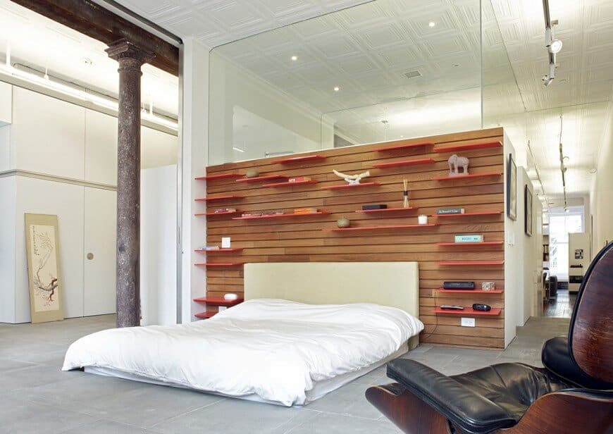 A grand primary bedroom features an accent shiplap wall with floating shelves. It includes concrete flooring and ornate ceiling tiles.