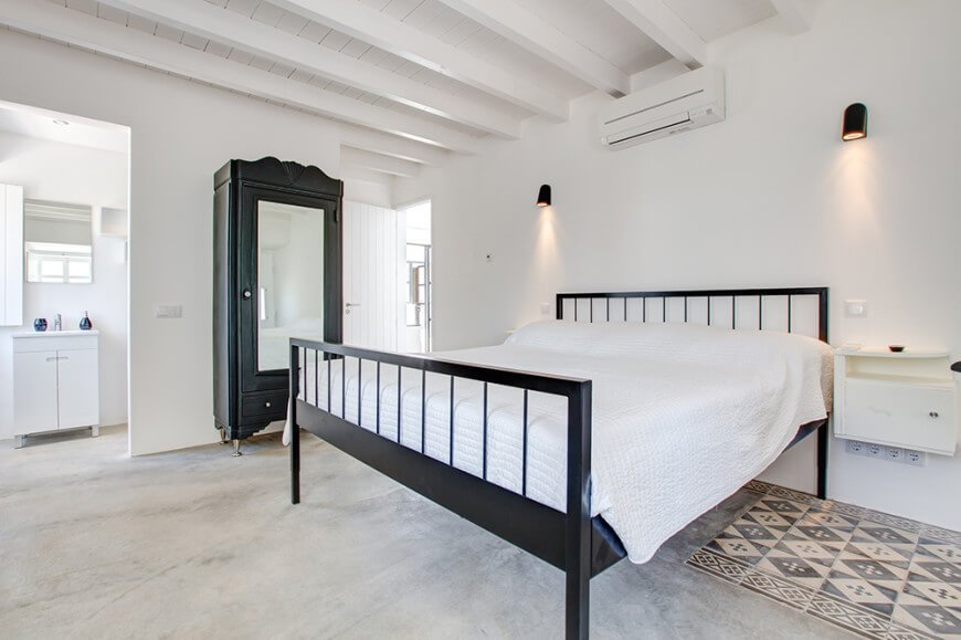 This master bedroom boasts carpet flooring, white walls with wall sconces and a white ceiling with exposed beams.