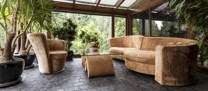 Sunroom and Conservatory room with beige sofa and graphite floor