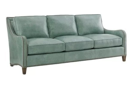 Aqua-colored leather sofa with plenty of movable cushions and dual row nailhead trims.
