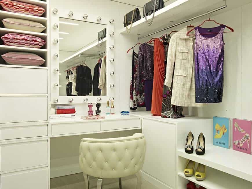 White chic women's bedroom closet with a carpet flooring and stylish ceiling lights.