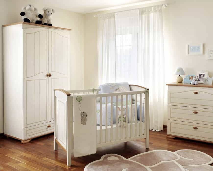 This nursery room features white walls and matching furniture set together with the hardwood flooring.