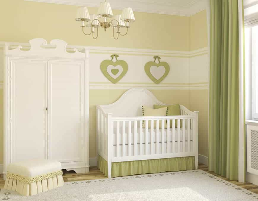 Classy nursery room with green shade and hardwood flooring topped by a rug.