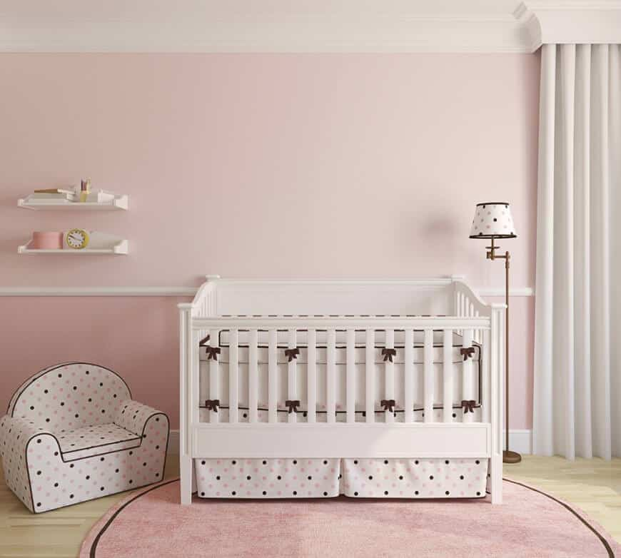 Pink themed nursery room for your baby girl. The flooring features a smooth vinyl topped by a pink round rug just below the crib. The walls are painted with pink adding a girlish touch to the room.