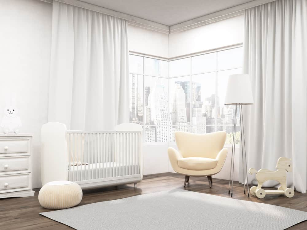 Large nursery room with white walls, curtains and rug along with the hardwood flooring.