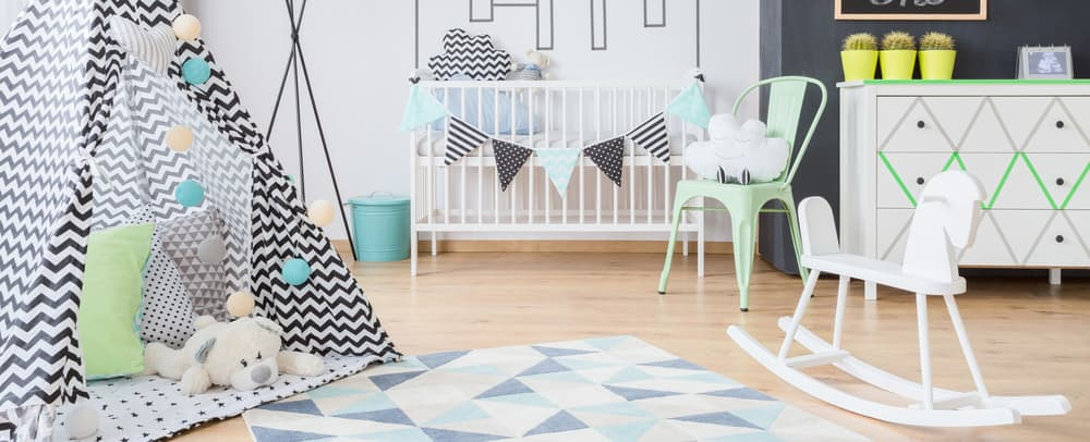 Large nursery room with white stylish walls, an interesting rug and a hardwood flooring.