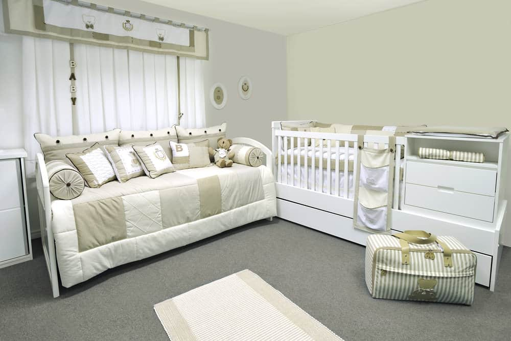 Large nursery room with carpet flooring and has a couch near the bed.