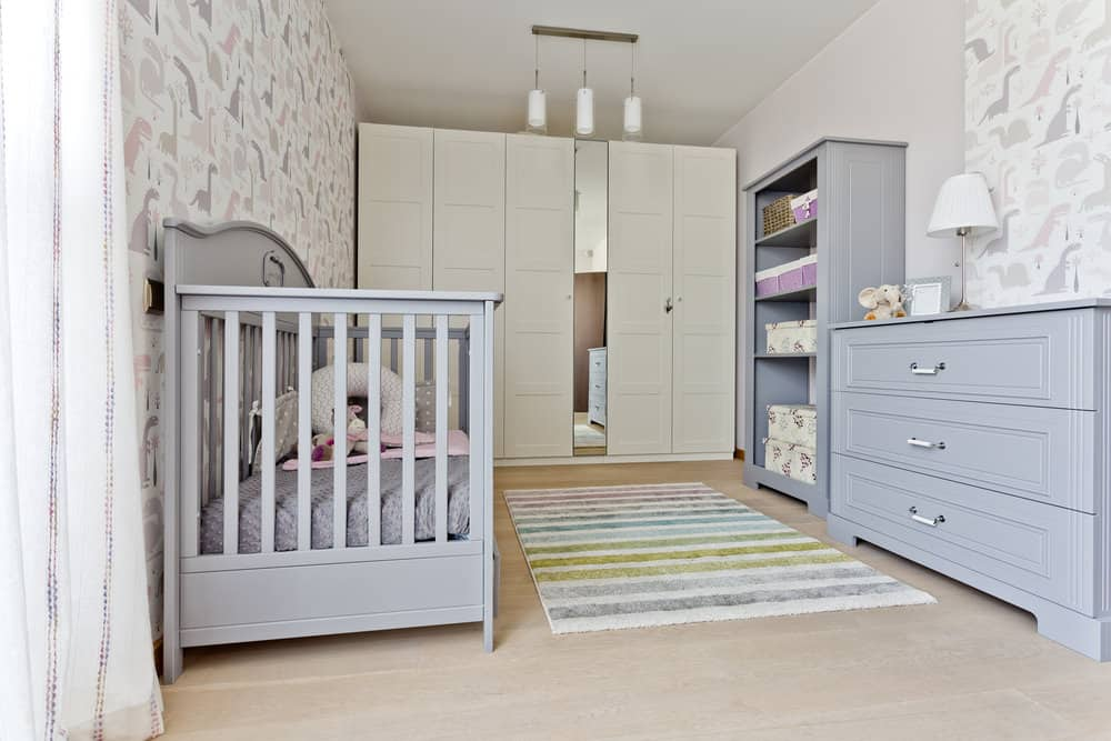 Nursery room with stylish walls and hardwood flooring.