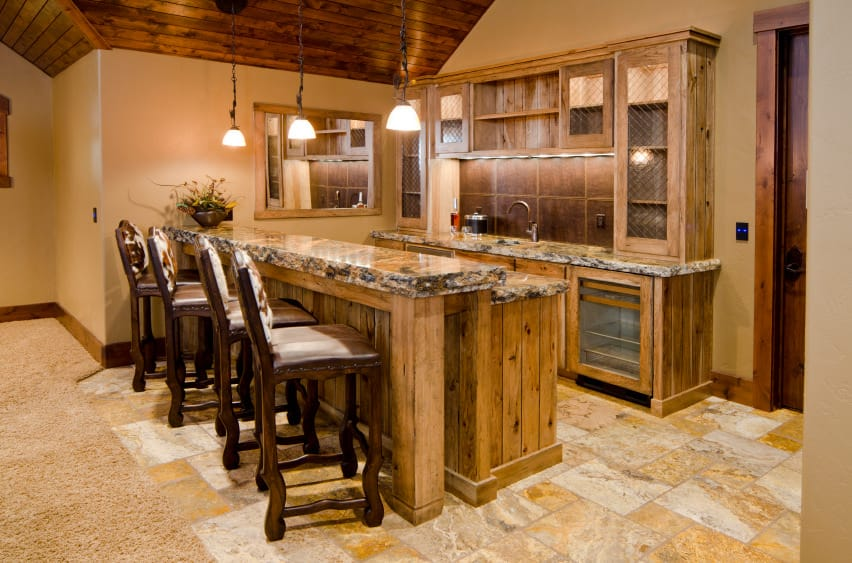 This bar features stylish countertops on wooden counters set on the tiles flooring. The pendant lights look perfect for this bar.