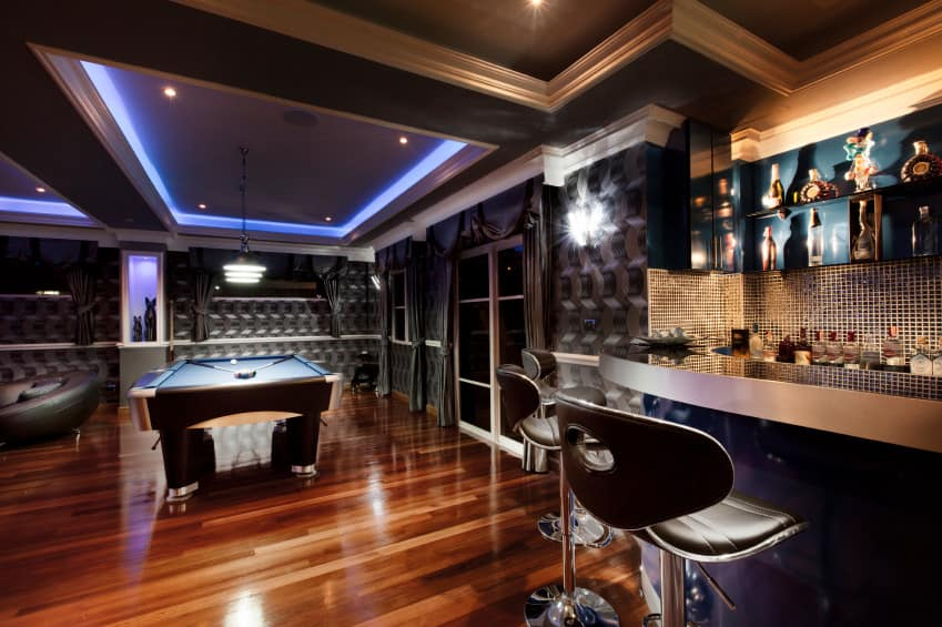 Large glamorous man cave with coffered ceiling design with built-in neon lighting. There's a sitting area, billiards table and glamorous bar decked out in silver and gold metallic color scheme. In fact, much of this man cave showcases metallic colors including chrome but tempered with polished hardwood flooring.