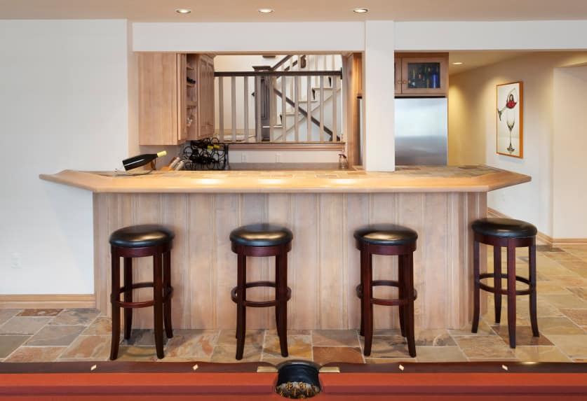 This bar features walnut finished cabinetry and counter set on the tiles flooring. The bar stools look perfect together with the bar.