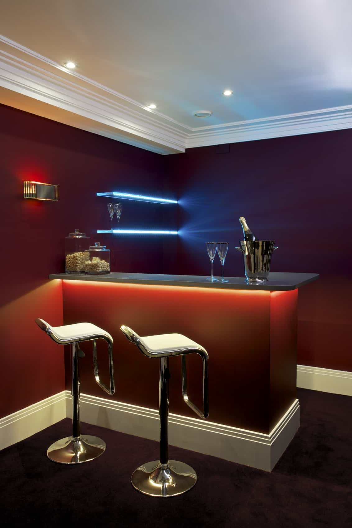 This bar features elegant carpet flooring and charming lighting all over the place. The red walls and counter, along with the couple of cozy bar stools add elegance to the room.