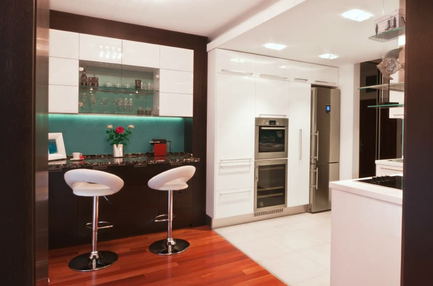 This small bar features cozy bar stools and lovely countertop set on an elegant flooring.