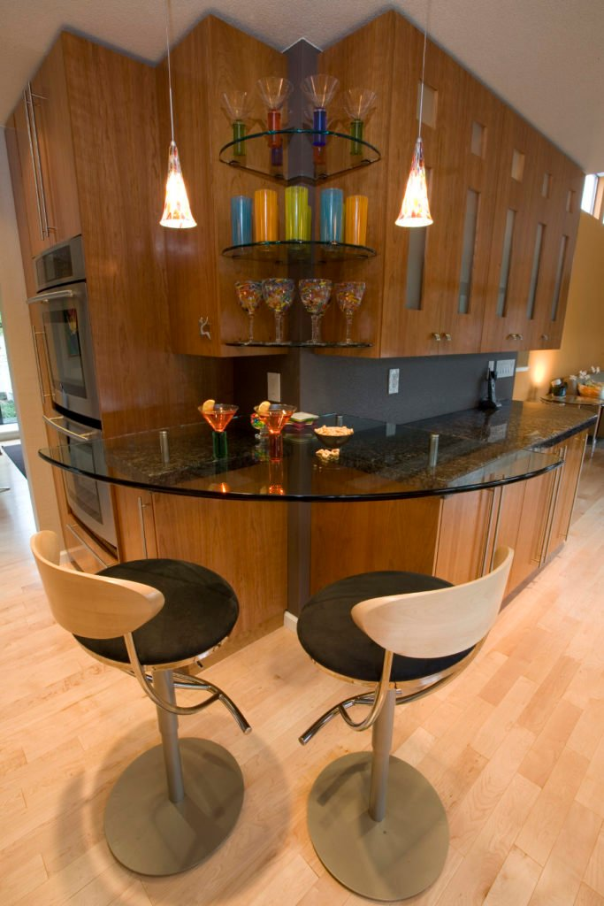 A close up look at this bar's beautiful countertop and shelves lighted by pendant lights.