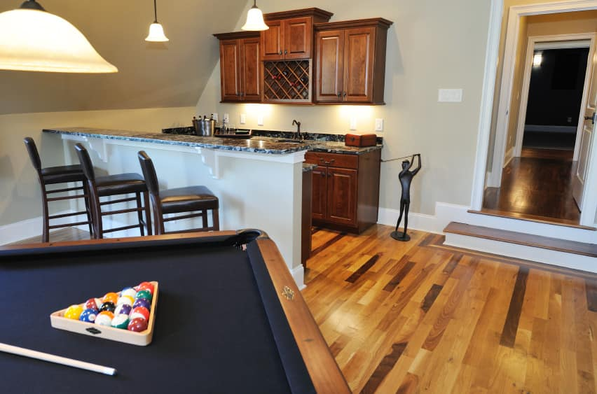 This bar features small counters with stylish countertops. There's a billiards pool as well, set on the hardwood flooring.