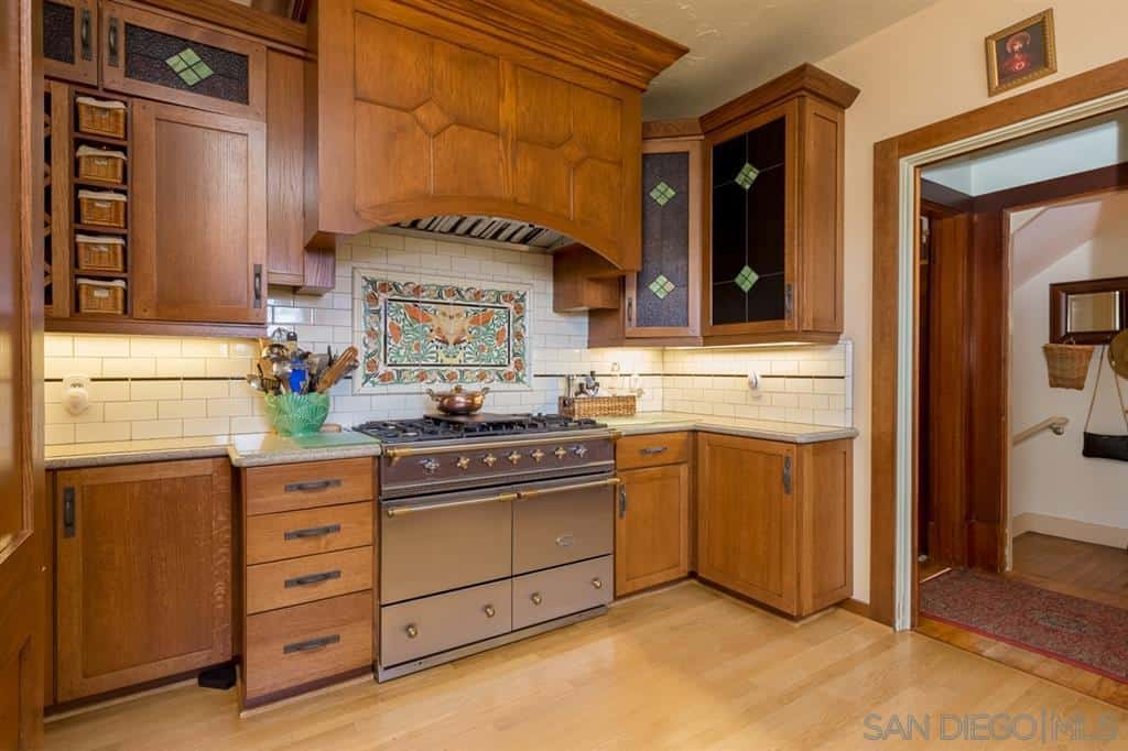 Colorful patterned tiles make up the backsplash of the cooking area giving this Craftsman-Style kitchen a homey warmth. The dark stained glass adorning the built-in cabinets is a nice artistic touch. The hardwood floors match well with the drawers and cabinets flanking the stove.