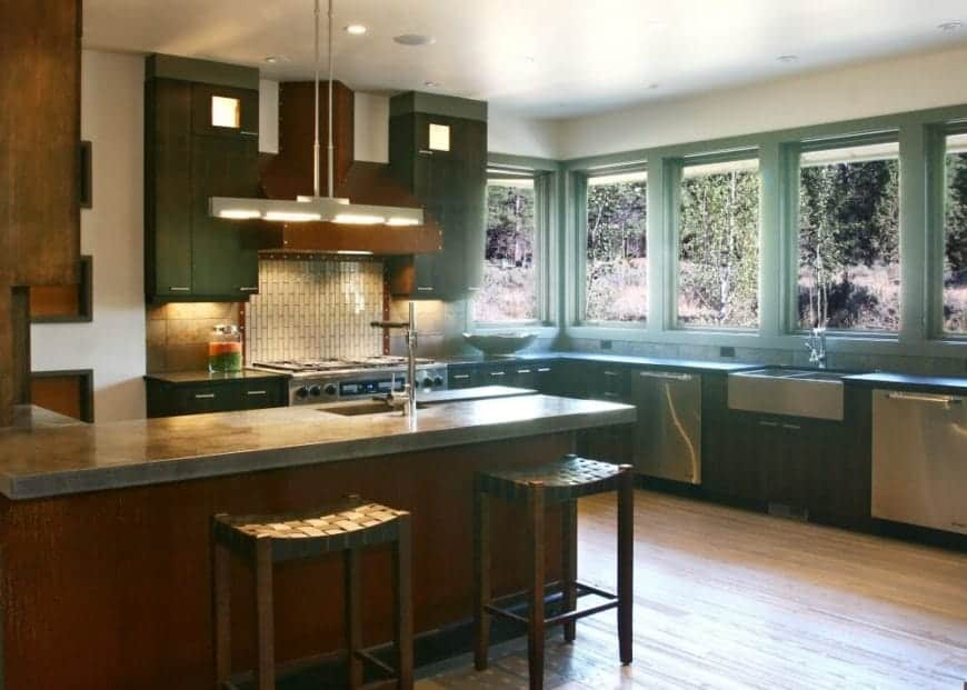 This is a Craftsman-Style kitchen that highlights the beauty of nature with its green hues and multiple windows that give a view of the surrounding foliage. This is augmented by the earthy tones of the wooden floors and peninsula then capped off with the white ceiling representing the sky.