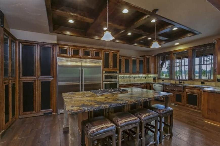 The moss-like patterns of the kitchen island's countertop are paired with a wooden coffered ceiling mounted with pin lights and pendant lights. The coffered ceiling matches well with the wooden finish of the cabinets lining the walls and the kitchen peninsula by the windows.