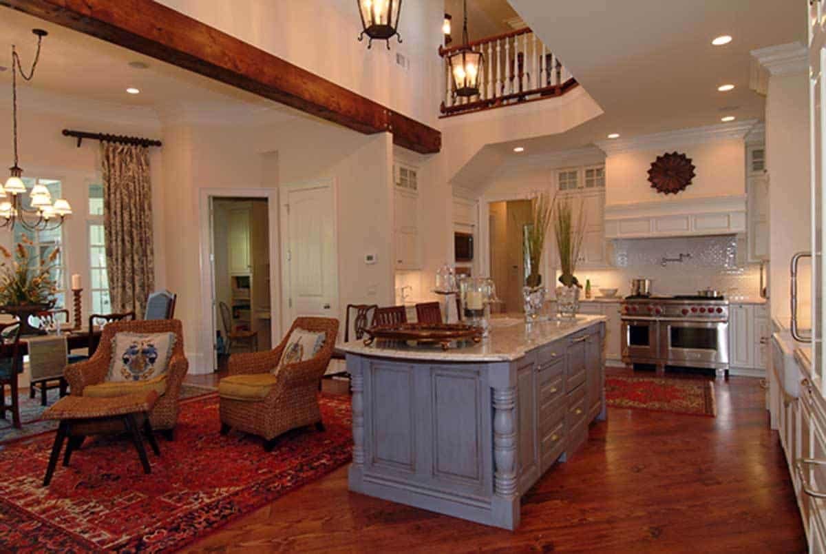 This is an airy Craftsman-Style kitchen that is open to the other sections of the house and has a high ceiling where a couple of pendant lantern-style lights hang. The beautiful gray hue of the kitchen island contrasts well with the redwood flooring while the white cabinets and drawers of the peninsula match with the white ceiling.