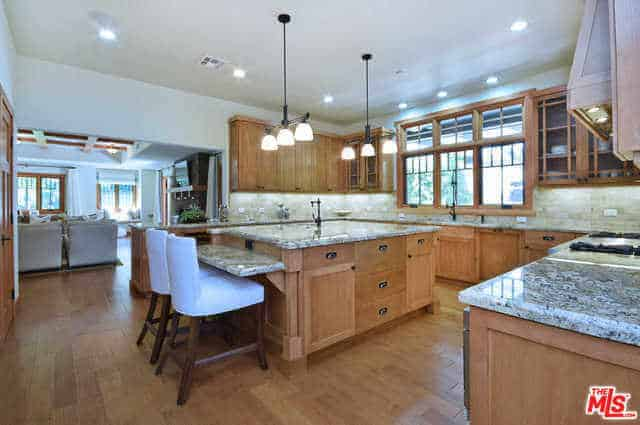 A lovely and bright Craftsman-Style kitchen that has a white ceiling that brightens up the room with its pin lights. This is augmented by three large windows and their natural lights that lighten up the wooden elements of the cabinets, drawers and the kitchen island with a whitish countertop that reflect those of the U-shaped peninsula.