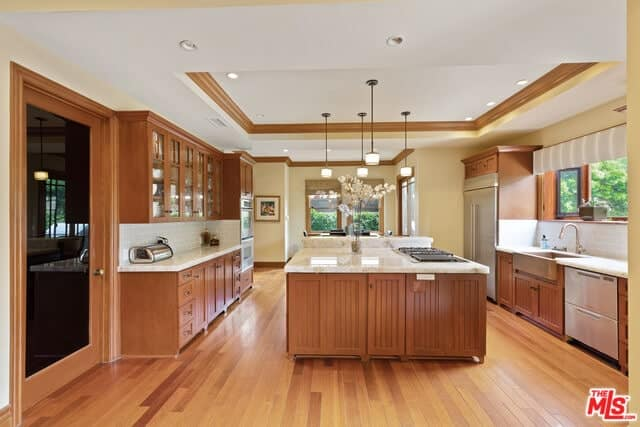 This Craftsman-Style kitchen has a tray ceiling that contrasts the hardwood floor. The hardwood floors reflect the wooden elements of the kitchen island and peninsulas. The natural lights and pendant lights play well on the white countertops and backsplash.