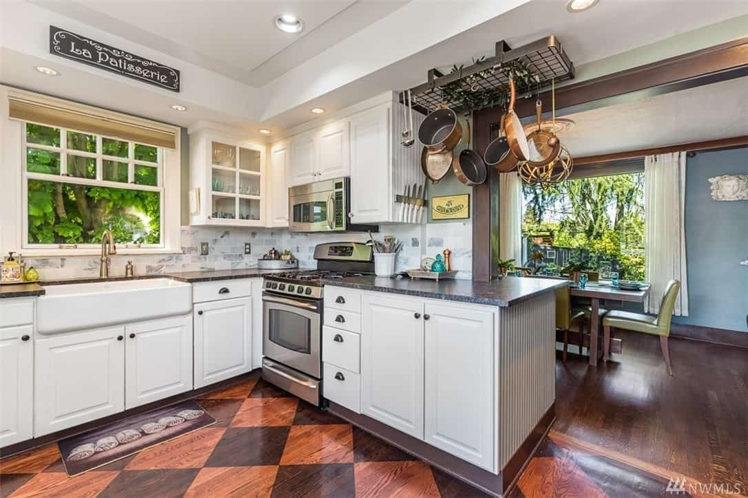 The beautiful hardwood flooring is accented with a chessboard design that contrasts the white tray ceiling. The white kitchen peninsula houses the sink and oven that are surrounded by white wooden cabinets and drawers with a dark countertop.