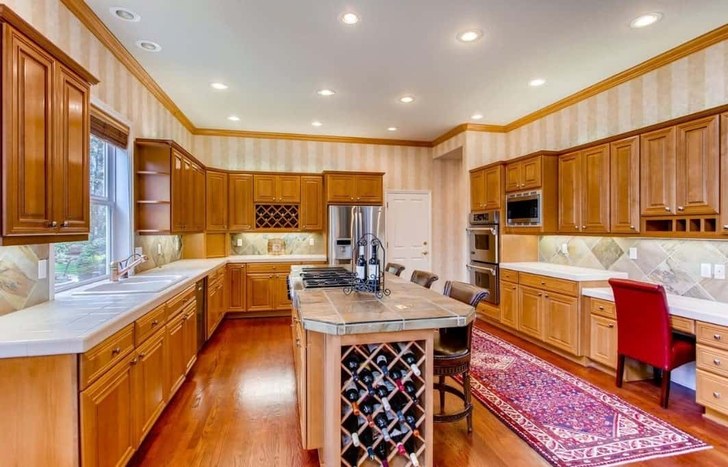 The colorful patterned rug and chic striped wallpaper of the upper layer of the walls are a good contrast to the wooden cabinets mounted over the kitchen peninsulas with drawers and cabinets of the same hue. The peninsulas are topped with white tiles that go well with the marble-like patterns of the backsplash tiles.