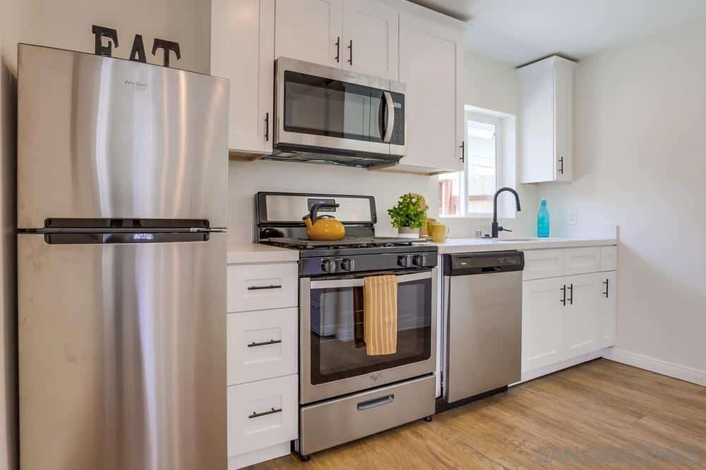 This is a simple and intimate Craftsman-Style kitchen that favors function over style. The modern elements come from simple lines and metallic fridge, oven, microwave, and dishwasher. These are augmented by the white wooden cabinets, drawers and hardwood flooring.