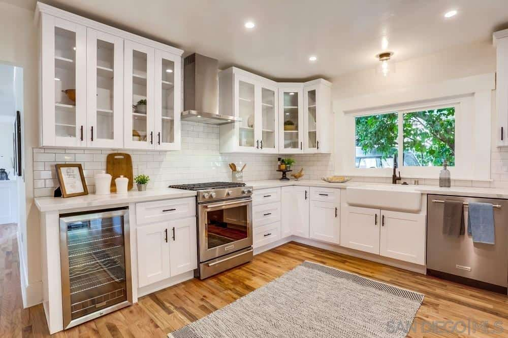 A grayish woven area rug is in the middle of the hardwood flooring of this kitchen. It pairs well with the modern appliances that are surrounded by white wooden cabinets and drawers of the kitchen peninsula which has a white countertop. The white elegance of this kitchen is augmented by the white ceiling and white-tiled backsplash with a brick wall design.